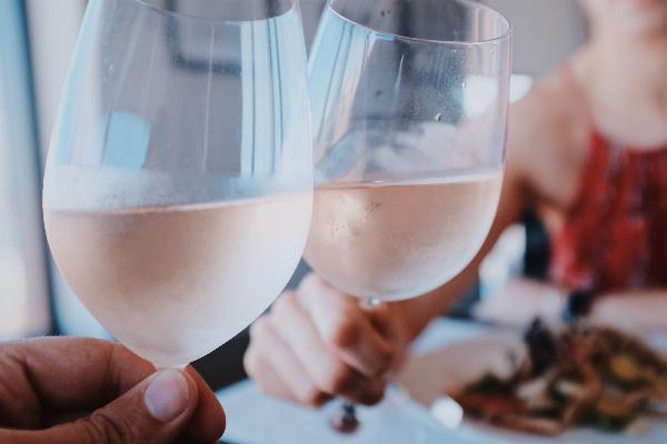 Cheers zwei Menschen stoßen mit Rose Wein an